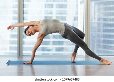 Young sporty woman doing yoga, Wild Thing pose, Flip-the-Dog exercise, Camatkarasana, working out wearing sportswear grey pants and top, indoor full length, yoga studio. Active life, wellness concept