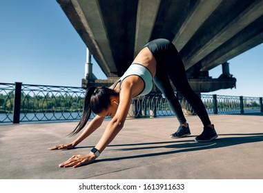 Young sporty woman doing yoga asana downward facing dog under industrial bridge. Adho Mukha Shvanasana
