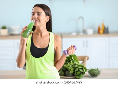 Young sporty woman drinking healthy vegetable juice in kitchen
