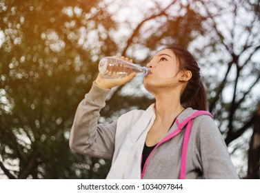 young sporty woman drinking water in the park