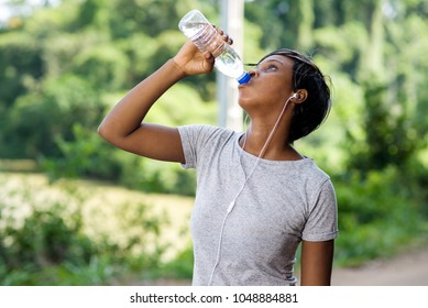 young sporty woman drinking water outdoors after fitness