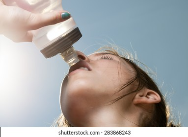 Young sporty woman drinking water from a bottle