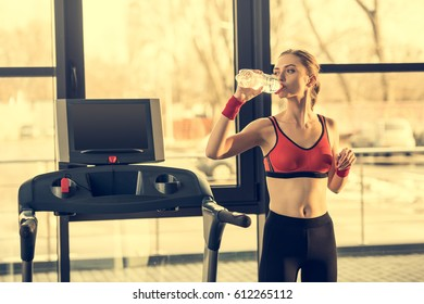 Young sporty woman drinking water from bottle while standing near trademill in gym