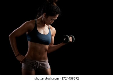 young sporty woman with  dumbbell on black background