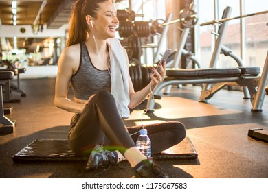 Young sporty woman with earphones listening to music on smart-phone during exercise break