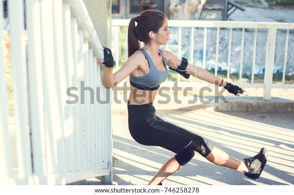 Young sporty woman exercising over fence outdoors.