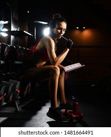 Young sporty woman experienced fitness trainer is sitting on barbells in gym hall and thinking over exercises plan. Diet and weight loss concept.