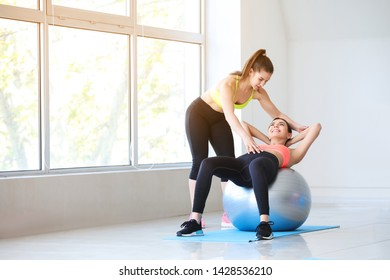 Young sporty woman with fitball doing exercises under supervision of her personal trainer in gym