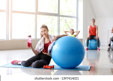 Young sporty woman with fitball drinking water in gym