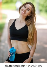 Young sporty woman with fitness beverage bottle