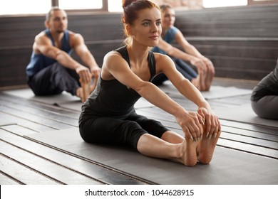 Young sporty woman and a group of people practicing yoga lesson, stretching in paschimottanasana exercise, Seated forward bend pose, working out, indoor, studio. Healthy lifestyle concept