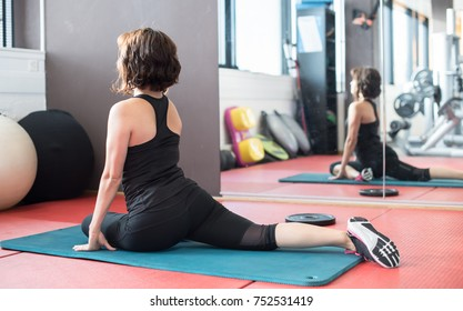 Young sporty woman in gym making stretching