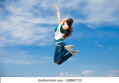 Young sporty woman jumping against the clear blue sky on the beach