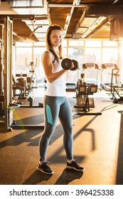 Young sporty woman lifting steel dumbbell in gym.
