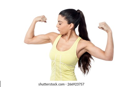 Young sporty woman looking at her biceps