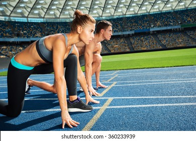 Young sporty woman and man are ready to run on racetrack. Fit well formed people are at large nice modern stadium