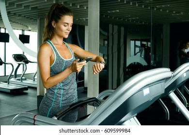 Young and sporty woman on treadmill in the gym