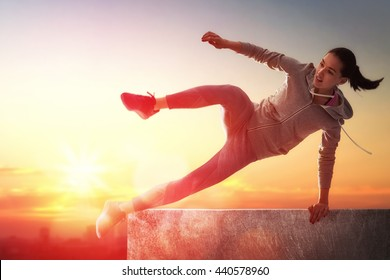 young sporty woman outdoors. the girl is engaged in parkour.