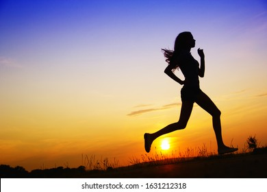 Young and sporty woman with perfect body running at sunset