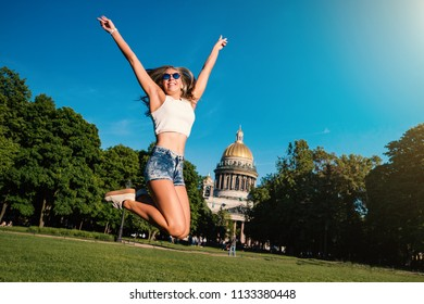 Young sporty woman portrait jumping outdoors in the park in a sunny day. Real life style moment captured. Saint Petersburg, Russia.