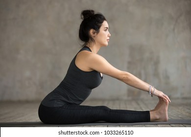 Young sporty woman practicing yoga, doing paschimottanasana exercise, Seated forward bend pose, working out, wearing sportswear, black pants and top, indoor full length, gray wall in yoga studio