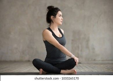 Young sporty woman practicing yoga, doing Revolved Easy exercise, Parivrtta Sukhasana pose, working out, wearing sportswear, black pants and top, indoor full length, gray wall, yoga studio