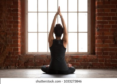 Young sporty woman practicing yoga, doing Sukhasana exercise, Easy Seat pose, working out, wearing sportswear, black pants and top, indoor full length, yoga studio window, rear view