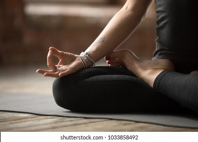 Young sporty woman practicing yoga, doing Padmasana exercise, Lotus pose, with mudra gesture, working out, wearing sportswear, black pants and top, indoor close up, yoga studio