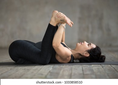Young sporty woman practicing yoga, doing Happy Baby exercise, Ananda Balasana pose, working out, wearing sportswear, black pants and top, indoor full length, gray wall in yoga studio