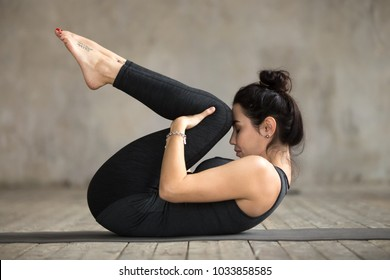 Young sporty woman practicing yoga, doing Knees to Chest exercise, Apanasana pose, working out, wearing sportswear, black pants and top, indoor full length, gray wall in yoga studio
