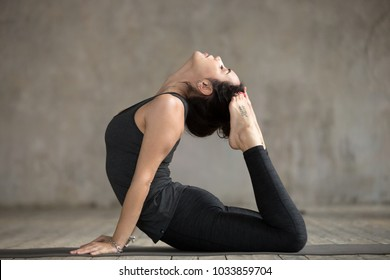 Young sporty woman practicing yoga, doing King Cobra exercise, Raja bhudjangasana pose, working out, wearing sportswear, black pants and top, indoor full length, gray wall in yoga studio