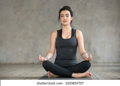 Young sporty woman practicing yoga, doing Sukhasana exercise, Easy Seat pose, working out, wearing sportswear, black pants and top, indoor full length, yoga studio