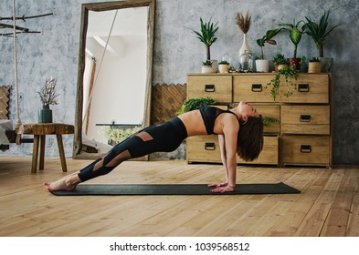 Young sporty woman practicing yoga, doing Purvottanasana exercise, Upward Plank pose, working out, wearing sportswear, black pants and top