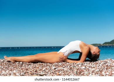 Young sporty woman practicing yoga, doing Matsyasana exercise, Fish pose, working out, wearing white sportswear, outdoor full length, on the beach, beautiful summer day