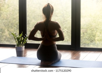 Young sporty woman practicing yoga, doing seiza exercise, vajrasana pose, working out, wearing sportswear, grey pants and top, indoor full length, yoga studio, rear view with Namaste behind the back