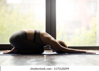 Young sporty woman practicing yoga, doing Child exercise, Balasana pose, working out, wearing sportswear, grey pants and top, indoor full length, yoga studio