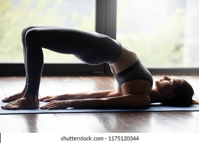 Young sporty woman practicing yoga, doing dvi pada pithasana exercise, Glute Bridge pose, working out, wearing sportswear, grey pants and top, indoor full length, yoga studio