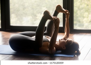 Young sporty woman practicing yoga, doing Happy Baby exercise, Ananda Balasana pose, working out, wearing sportswear, grey pants and top, indoor full length, yoga studio