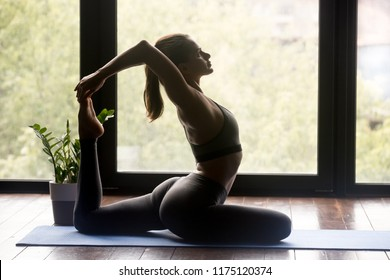 Young sporty woman practicing yoga, doing One Legged King Pigeon exercise, Eka Pada Rajakapotasana pose, working out, wearing sportswear, grey pants and top, indoor full length, yoga studio