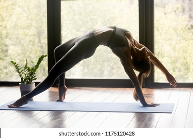 Young sporty woman practicing yoga, doing Wild Thing, Flip-the-Dog exercise, Camatkarasana pose, working out, wearing sportswear, grey pants and top, indoor full length, yoga studio