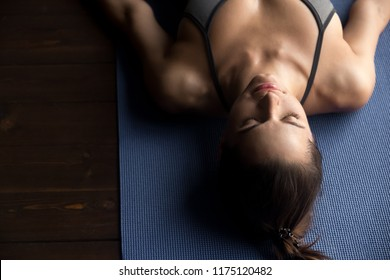 Young sporty woman practicing yoga, doing Dead Body, Savasana exercise, Corpse pose, working out, wearing sportswear, grey top, indoor close up, yoga studio, top view