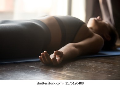 Young sporty woman practicing yoga, doing Dead Body, Savasana exercise, Corpse pose, working out, wearing sportswear, grey pants and top, indoor close up view, yoga studio, focus on mudra gesture