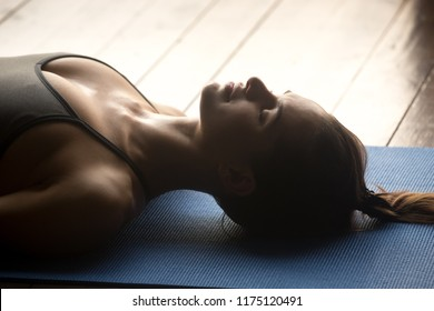 Young sporty woman practicing yoga, doing Dead Body, Savasana exercise, Corpse pose, working out, wearing sportswear, grey top, indoor close up, yoga studio