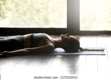 Young sporty woman practicing yoga, doing Dead Body, Savasana exercise, Corpse pose, working out, wearing sportswear, grey pants and top, indoor close up, yoga studio