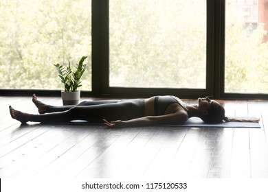 Young sporty woman practicing yoga, doing Dead Body, Savasana exercise, Corpse pose, working out, wearing sportswear, grey pants and top, indoor full length, yoga studio