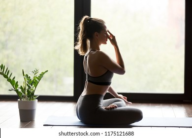Young sporty woman practicing yoga, doing Alternate Nostril Breathing exercise, nadi shodhana pranayama pose, working out, wearing sportswear, grey pants and top, indoor full length, yoga studio