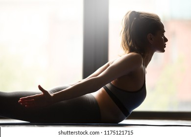 Young sporty woman practicing yoga, doing Double Leg Kicks exercise, Salabhasana pose, working out, wearing sportswear, grey pants and top, indoor close up, yoga studio