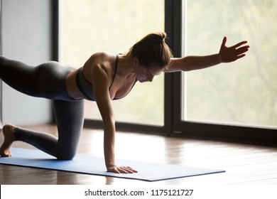 Young sporty woman practicing yoga, doing Donkey, Kick exercise, Bird dog pose, working out, wearing sportswear, grey pants and top, indoor, yoga studio