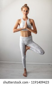 Young sporty woman practicing yoga, standing Tree Pose pose, working out against white vackgroundr, indoor full length, window sill