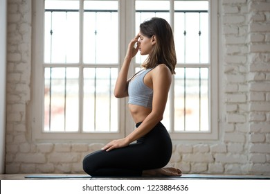 Young sporty woman practicing yoga, doing Alternate Nostril Breathing exercise, nadi shodhana pranayama pose, working out, wearing sportswear, indoor full length, white yoga studio, side view